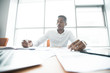 Serious busy African-American-American male manager in white shirt sitting at table full of papers and making notes in diary while doing business analysis in office.
