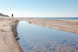 small silhouette of a man on a bright wild beach with a small lake by the blue sea, Curonian Spit National Park