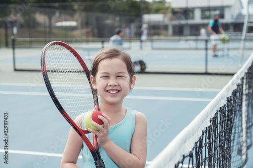 Young Asian girl tennis player on outdoor blue court