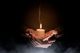 Hands holding candle over dark background - 229123025