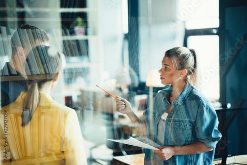 Leinwandbild Motiv Startup and millenial business concept. Woman manager explaining tasks to her team