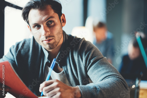 Leinwandbild Motiv Startup and millenial business concept. Portrait of thinking manager working with note pad in office