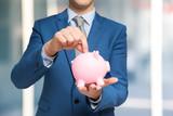 Man putting money in a piggy bank