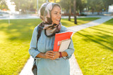 Muslim young woman walking outdoors holding books. - 229148834