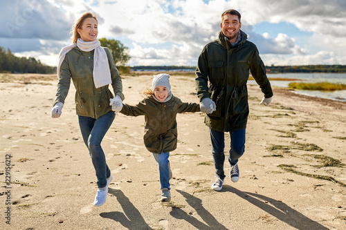 Leinwandbild Motiv family, leisure and people concept - happy mother, father and little daughter running along autumn beach