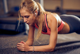 Woman doing planks on gym floor. Healthy lifestyle concept. - 229157242