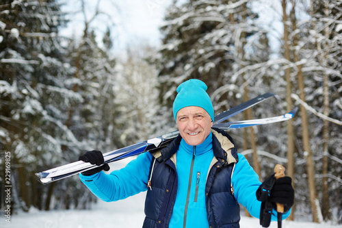 Happy senior sportsman with skis looking at you while standing in forest on winter day - 229169825