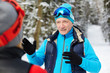 Active senior man in skiing sportswear explaining something to his wife during training in winter forest