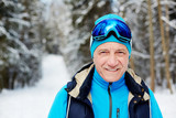 Active senior man in sportswear and skiing goggles looking at you during training in winter forest