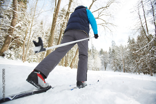 Sticker Rear view of sportsman in activewear moving on skis in snowdrift in winter forest