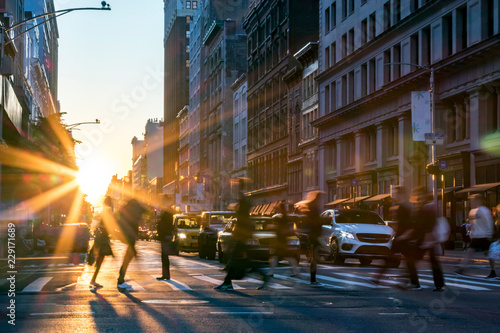 Leinwanddruck Bild Rays of sunlight shine on the busy people walking across an intersection in Midtown Manhattan in New York City