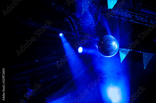 Disco ball with bright blue rays, night party background photo - 229173659