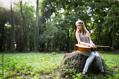 Heartbroken woman in nature with guitar - 229174813