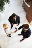 High angle view of business partners have signed a contract and shaking hands at office - 229177258