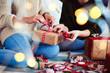 Leinwanddruck Bild - Two friends preparing christmas presents for Christmas
