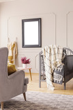 Mockup on the wall of mid century baby room with grey armchair, crib with blankets and heather in white pot on the table