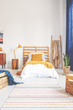 Yellow pillow and blanket on comfortable white wooden bed in teenager bedroom with stripped carpet on the floor - 229182671