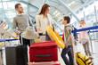 Familie und zwei Kinder im Flughafen Terminal