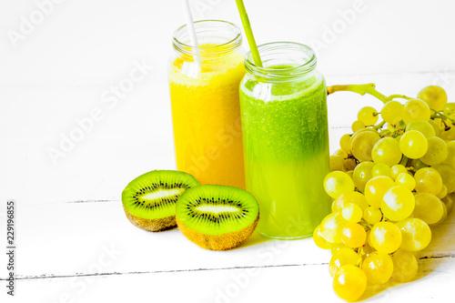 Leinwanddruck Bild Fresh detox juices in glass bottles on white background