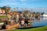 Kutterflotte im Hafen von Greetsiel bei blauem Himmel - 229199226