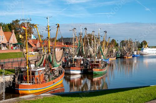 Leinwanddruck Bild Kutterflotte im Hafen von Greetsiel bei blauem Himmel