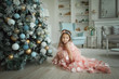 Cheerful child girl with Christmas tree at home