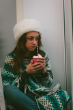 Lonely christmas. Beautiful girl sitting alone during christmas day. - 229202078