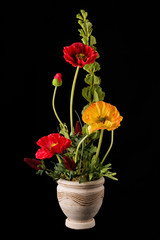 Floral arrangement from artificial poppy flowers in old ceramic flower pot.