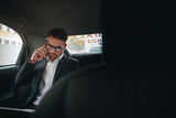 Businessman doing office work while travelling to office in a ca - 229206204