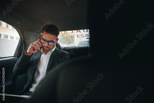 Wall mural Businessman doing office work while travelling to office in a ca