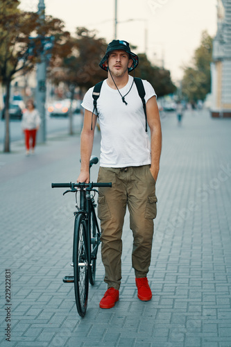 Portrait of young man walking with thoughtfully classic bicycle on city streets