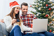 Leinwandbild Motiv Couple sitting on sofa and doing christmas shopping online with credit card and laptop