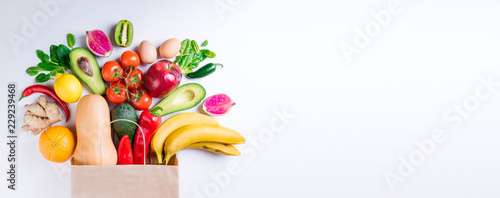 Healthy food in paper bag fruits and vegetables on white. Concept healthy food background. Vegetarian food. Shopping food supermarket. Long web format
