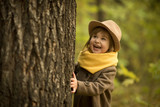 Little cute baby girl is walking, smiling, playing in autumn park outdoor nature yellow plants trees - 229239663