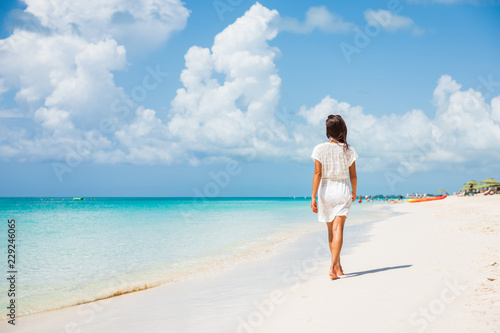 Leinwandbild Motiv Caribbean beach luxury vacation summer holiday woman walking on perfect white sand tourist destination.