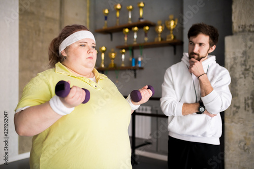 Portrait of motivated overweight woman working out with dumbbells during weight loss training with fitness instructor, copy space