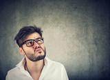 Doubtful man making grimace while thinking