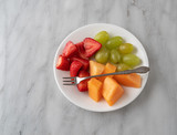 Overhead view of strawberries grapes and cut cantaloupe on a white plate with a small fruit fork atop the food on a gray marble counter top.