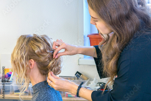 Young girl - hairdresser creates a hairstyle for a blonde girl