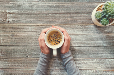 Person holding a coffee mug on a wooden desk overhead view