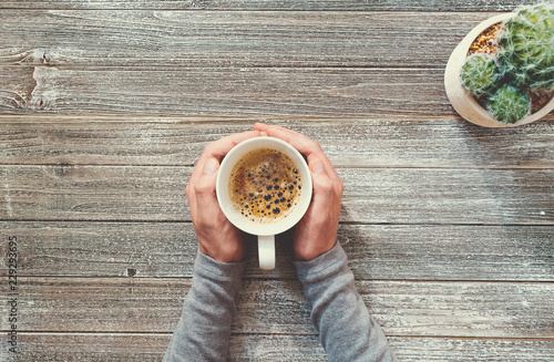 Person holding a coffee mug on a wooden desk overhead view - 229293695