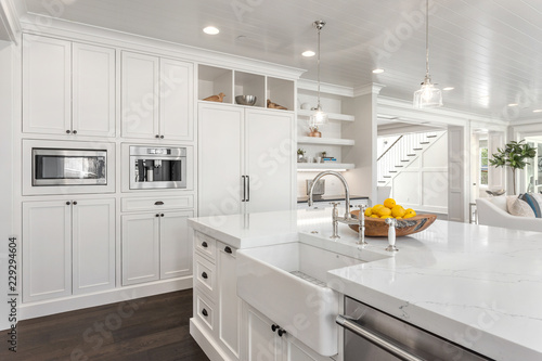 White Kitchen Detail in New Luxury Home: Shows Sink, Dishwasher, Refrigerator, Microwave, and Coffee Maker