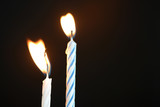 Two birthday candles against a dark background close up - 229298490