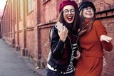 Two joyful young girls dancing while listening to music on smartphone, city outdoor. - 229310269