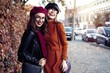 Leinwandbild Motiv Outdoors fashion portrait young pretty best girls friends in friendly hug. Walking at the city. Posing at the street. Wearing stylish outerwear and hats. Bright make up. Positive emotions.