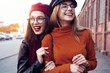 Outdoors fashion portrait young pretty best girls friends in friendly hug. Walking at the city. Posing at the street. Wearing stylish outerwear and hats. Bright make up. Positive emotions.