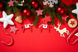 beautiful Christmas baubles, spruce, stars and wooden horses on a red background