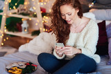 Girl with mobile phone spending christmas time in bed - 229329651