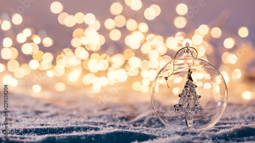 Leinwanddruck Bild Christmas glass ball with tree in it on winter background.