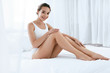 Body Skin Care. Beautiful Woman Touching Long Legs On White Bed